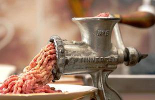 Close-up de carne de molienda de molino de acero inoxidable tradicional foto