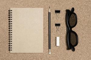 Bloc de notas con lápiz sobre fondo de tablero de corcho