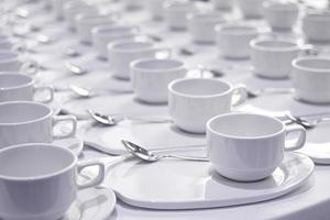 Stacks of coffee cups  with silver teaspoons  prepare for meetin photo