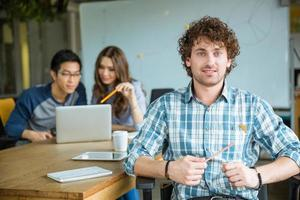 Attractive cheerful young curly malestudying with students in classroom photo