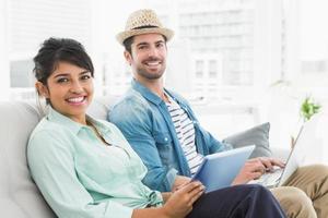 compañeros de trabajo sonrientes con tableta y portátil en el sofá