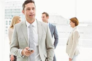 Businessman text messaging with colleagues in meeting behind photo
