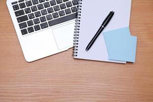Office table with laptop, notepad and coffee cup photo