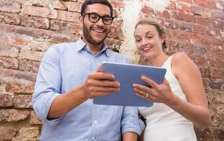 Colleagues using digital tablet against brick wall