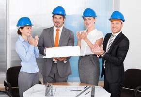 Colleagues Clapping For Man Holding Model