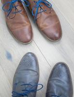 two pairs of shoes on  a wooden floor photo