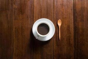Coffee cup on wooden background, top view