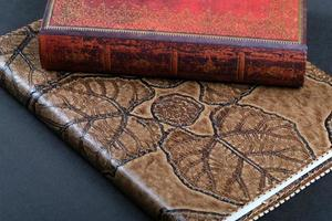 caderno de capa de couro dois em cima da mesa