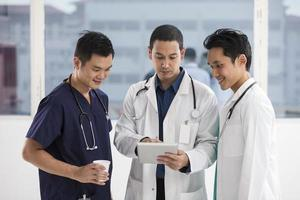 Team of male doctors using a digital tablet photo