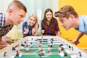amigos felices jugando hockey de mesa foto