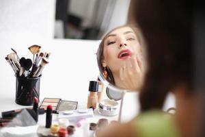jonge mooie vrouw die make-up in de buurt van spiegel
