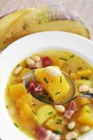 Swede soup with white beans and bacon, spoon and plate