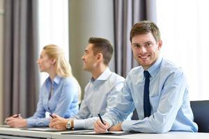 Grupo de empresarios sonrientes reunidos en la oficina