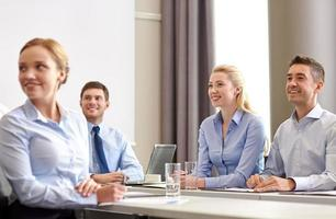 group of smiling businesspeople meeting in office photo