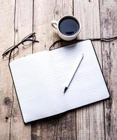 glasses on notebook with pen and cup of coffee