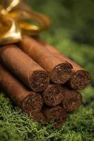 regalo de cigarros cubanos con cinta dorada sobre musgo natural foto