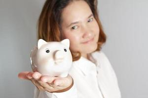 Smiling woman holding piggy bank in hands photo