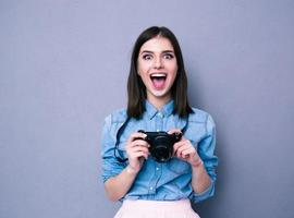 Amazed young pretty woman holding camera photo