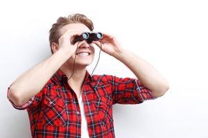 chico sonriente interesado mirando a través de binoculares foto
