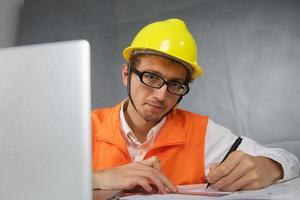 Cute young builder with pen photo