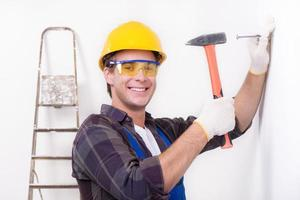 Smiling repairman nailing