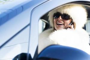 Woman in white coat on the phone smiling
