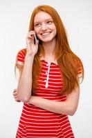 Happy young woman with long red hair talking on cellphone photo