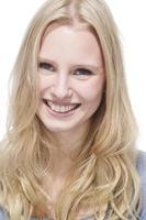 joven mujer rubia sonriendo contra el retrato de fondo blanco