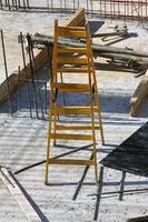 escalera amarilla en el sitio de construcción