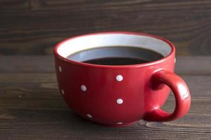 Red ceramic cup of coffee with polka dots