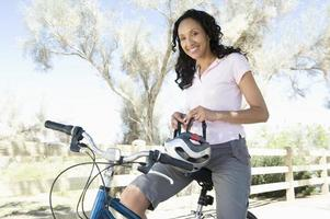 African American Female Sitting On Cycle With Helmet In Hand photo
