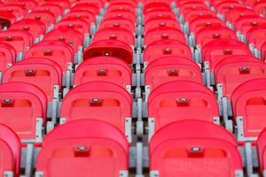 close up of red folded up seats in football stadium