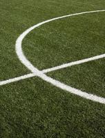 Part of soccer field with green synthetic grass closeup photo
