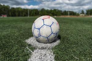 Worn soccer ball at kickoff spot on turf