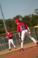 Lanzador de béisbol de la liga pequeña mirando al bateador. foto