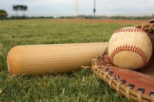 Baseball, bat, and glove on the grass