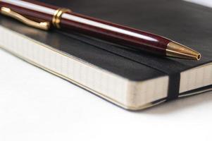 primer plano de una pluma y cuaderno