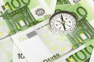 muchos billetes de banco en euros y una brújula foto