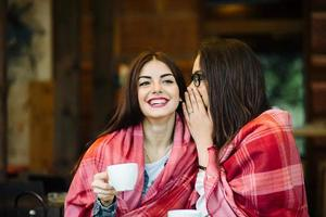 Two young and beautiful girls gossiping photo