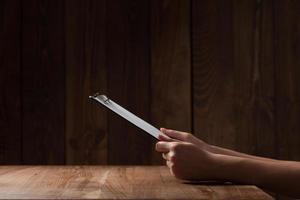 Frauenhand, die Papier über Holztisch hält