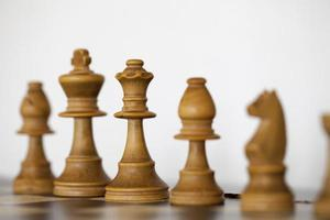 Wooden white chess pieces on chess board