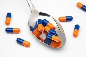 cuchara con capsulas medicas foto
