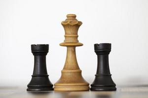 Wooden white queen and black rooks chess pieces