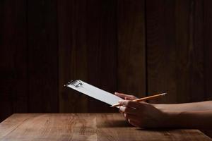 Nahaufnahme der Hand der Frau, die auf Papier über Holztisch schreibt