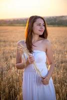 girl with a bouquet of ears at sunset photo