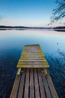 paisaje del lago con pequeño muelle de madera fotografiado en larga exposición