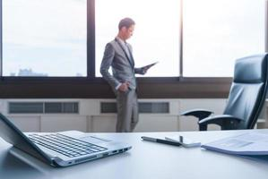 business man standing at window using tablet behind working desk