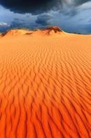 dunes in sand desert under dark sky before thunder storm