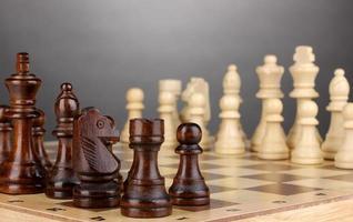 tablero de ajedrez con piezas de ajedrez sobre fondo gris foto