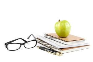 apilar elegante cuaderno, bolígrafo y gafas. suministros de oficina o escuela